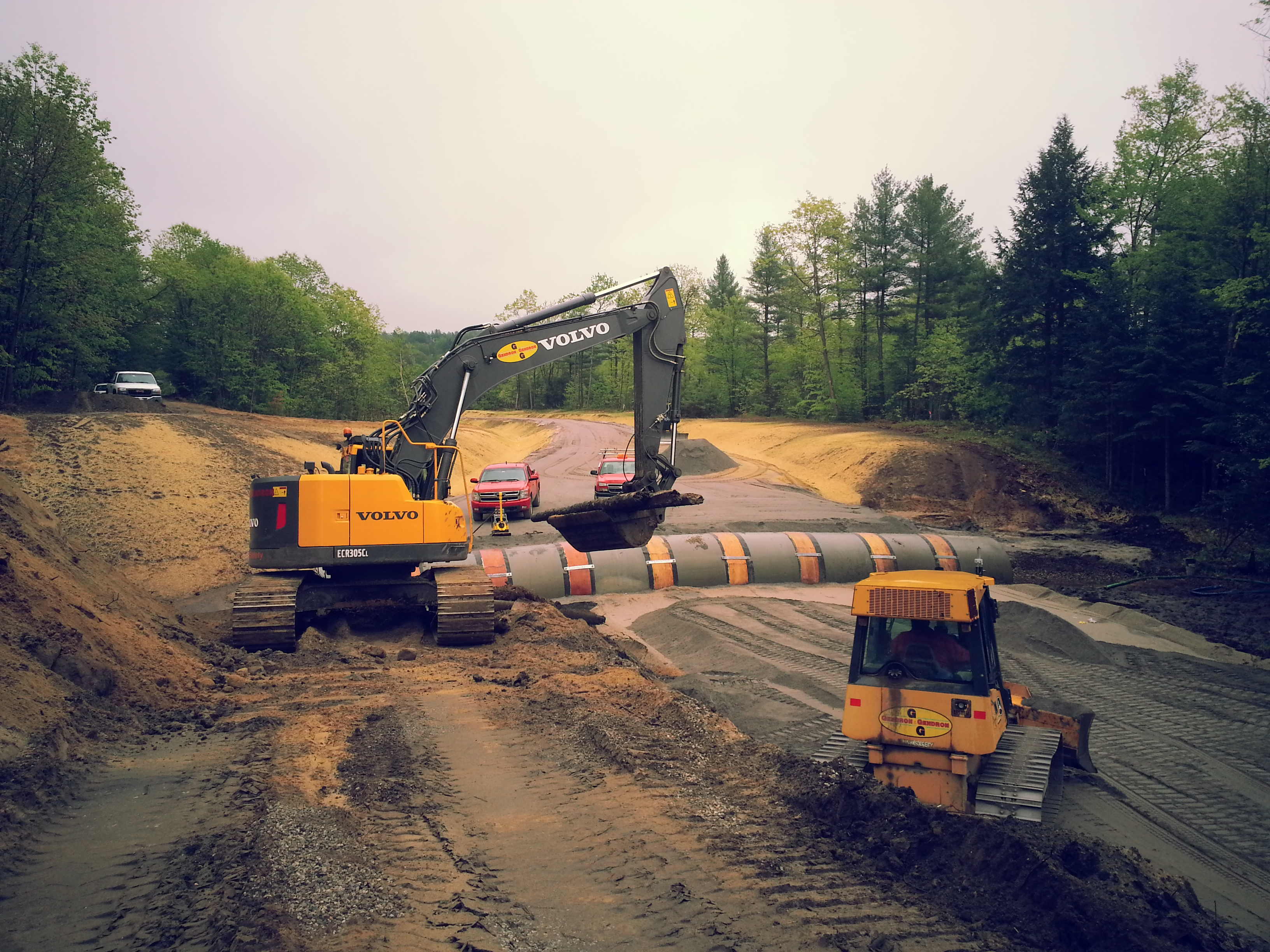 Excavation equipment preparing gravel base in a roadway bed around a recently installed culvert.
